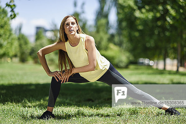 Woman exercising on a meadow in a park