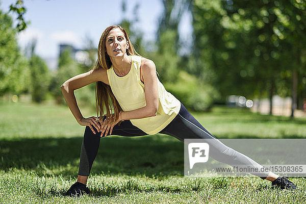 Frau übt auf einer Wiese in einem Park