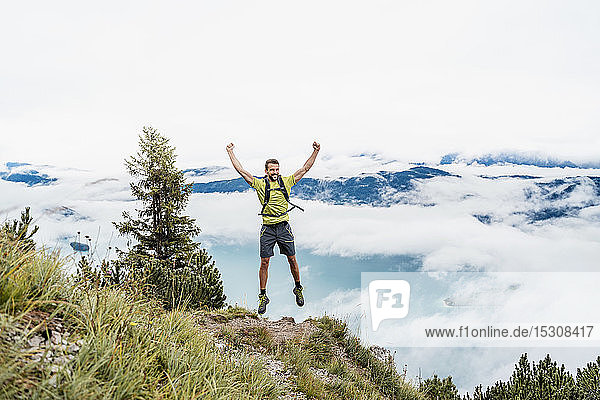Happy young man with raised arms on a hiking trip in the mountains  Herzogstand  Bavaria  Germany