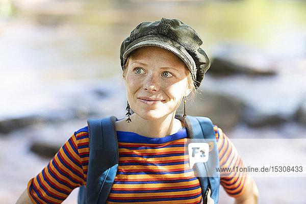 Porträt einer lächelnden Frau mit Rucksack an einem Flussufer