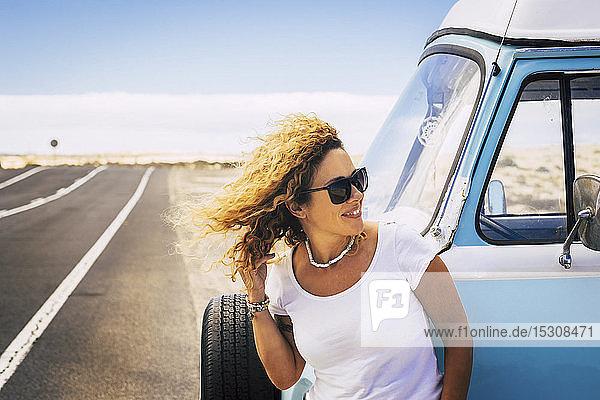 Frau lehnt auf Lieferwagen und schaut zur Seite