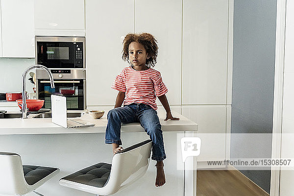 Girl with laptop sitting on kitchen counter