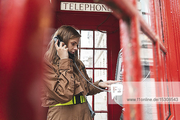 Young woma nmaking a call from a red phone booth in the city  London  UK