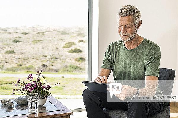 Senior man using tablet at home