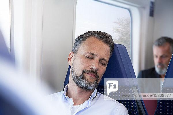 Reifer Mann sitzt im Zug und schläft