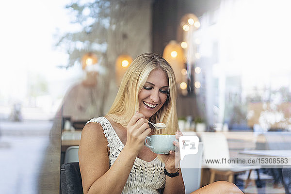 Porträt einer glücklichen blonden Frau  die in einem Cafe Cappuccino trinkt