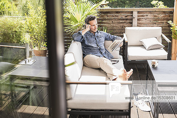 Confident man relaxing on the terrace  reading book