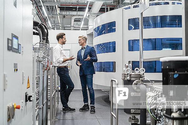 Zwei Geschäftsleute im Gespräch in einer modernen Fabrik