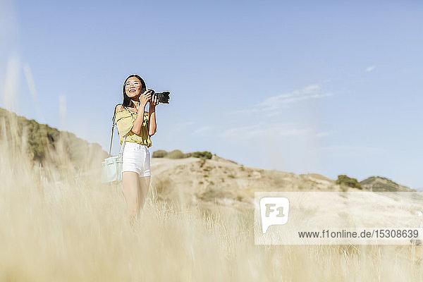 Junge Frau beim Fotografieren in abgelegener Landschaft,  Granada,  Spanien