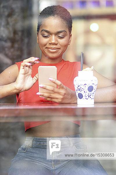 Porträt einer lächelnden jungen Frau in einer Bar mit Blick auf ihr Handy