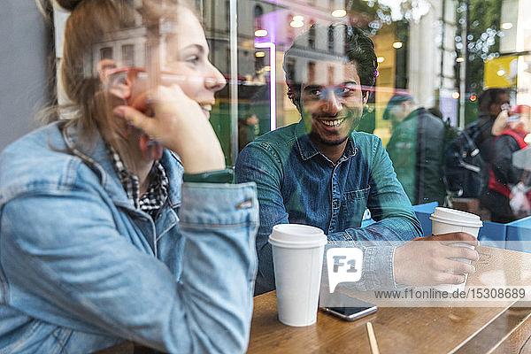 Porträt eines lächelnden jungen Mannes in einem Café  der einer jungen Frau zuhört