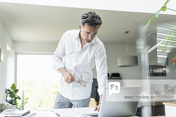 Architect working on blueprint in a bright office  using laptop