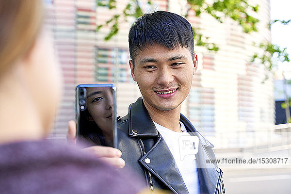 Smiling young man taking a cell phone picture of woman in Barcelona  Spain