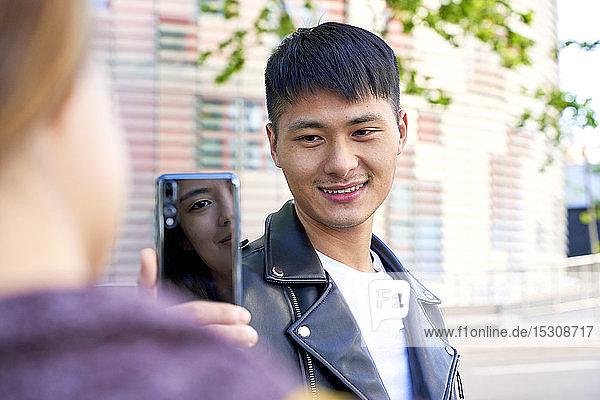 Lächelnder junger Mann macht ein Handyfoto von Frau in Barcelona  Spanien