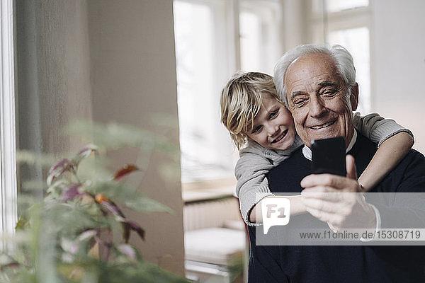 Glücklicher Großvater und Enkel telefonieren zu Hause