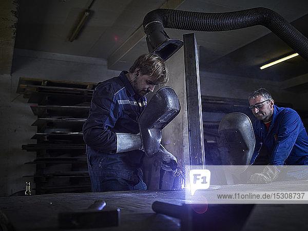 Worker welding in factory