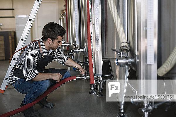 Jungunternehmer arbeitet am Tank einer Brauerei