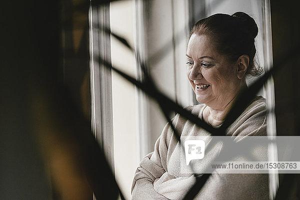 Glückliche ältere Frau  die zu Hause aus dem Fenster schaut