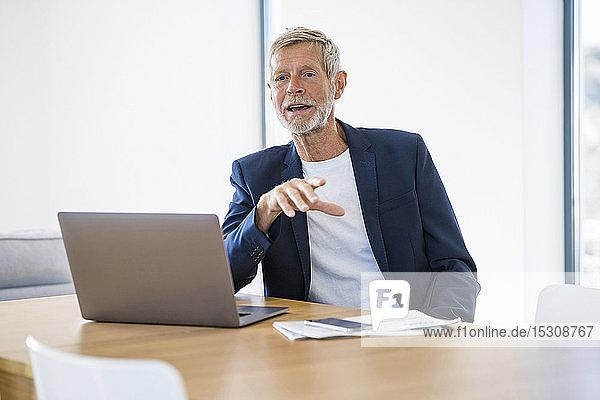 Senior businessman with laptop sitting at desk at home talking
