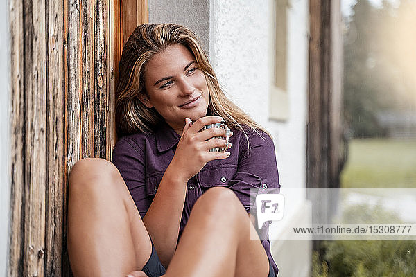 Young woman having a drink at a farmhouse during a hiking trip  Vorderriss  Bavaria  Germany