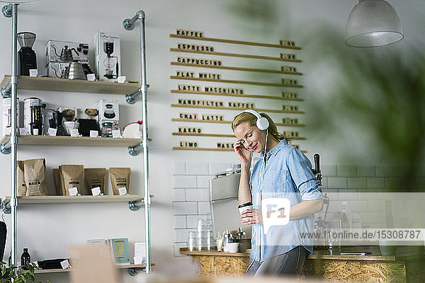 Young woman listening music  wearing headphones  standing in coffee shop