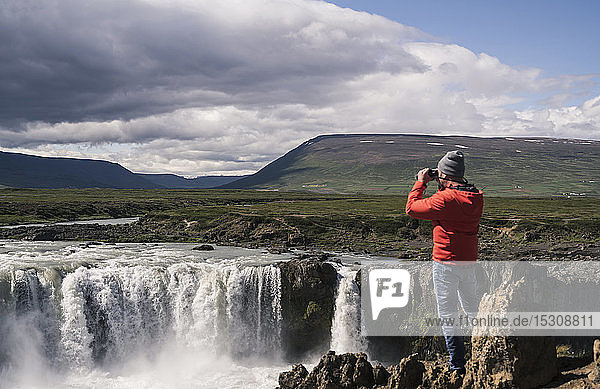 Man looking at Godafoss waterfalls  Iceland  with binoculars