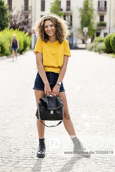 Porträt einer lächelnden jungen Frau  die auf einem Weg in der Stadt steht