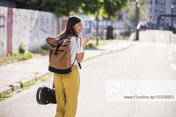 Junge Frau trägt Geigenkoffer mit Handy auf der Strasse