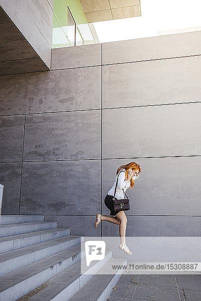 Geschäftsfrau benutzt Smartphone und springt die Treppe hinunter
