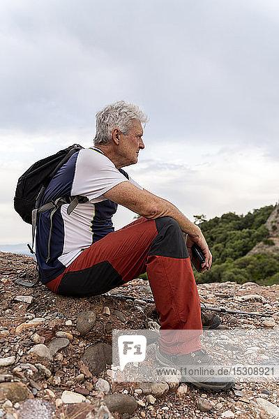 Älterer Mann sitzt auf dem Hügel