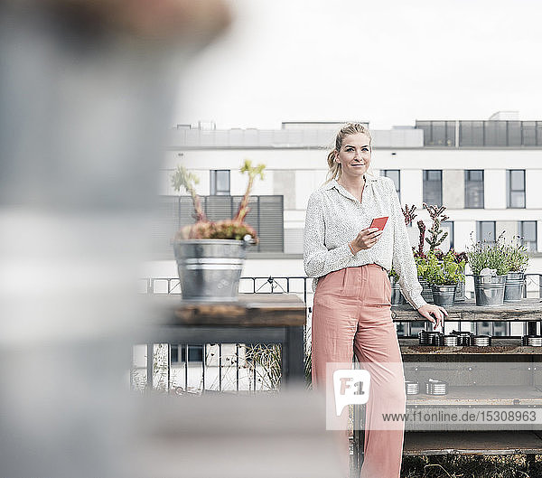 Portrait of casual businesswoman with cell phone on roof terrace