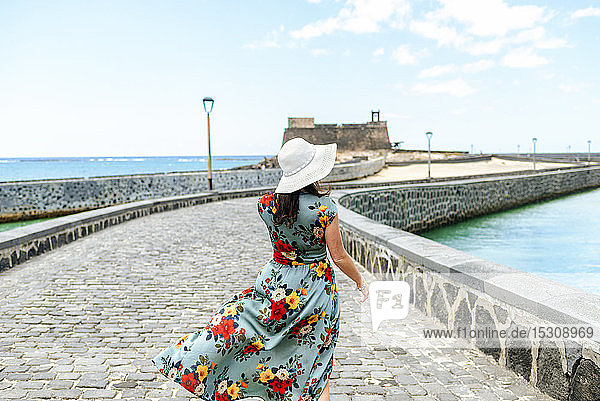Rückansicht einer Frau mit weißem Sonnenhut in Arrecife  Spanien