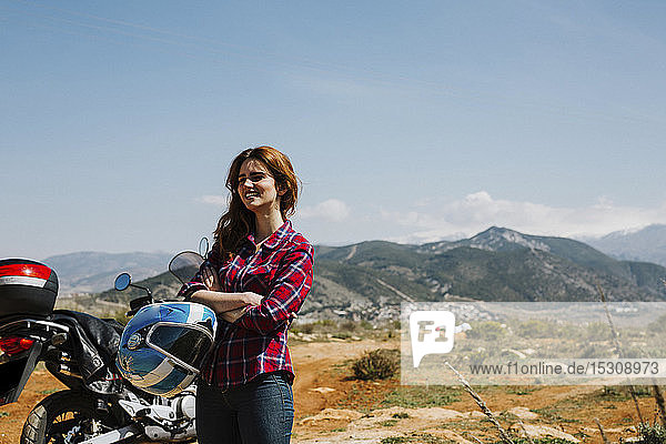 Happy redheaded woman with motorbike enjoying view  Andalusia  Spain