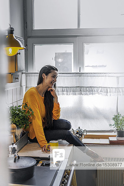 Happy young woman sitting on kitchen counter at home