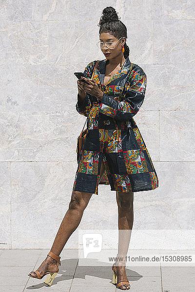 Porträt einer schicken Frau in gemustertem Kleid mit Mobiltelefon
