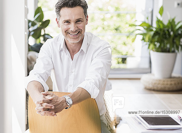 Mature man sitting on chair backwards  smiling