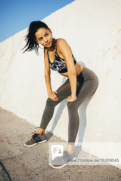 Woman during workout  leaning on a wall