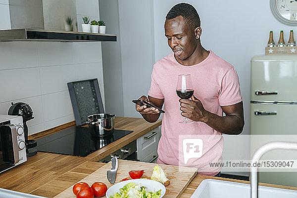 Junger Mann mit Weinglas  der während der Salatzubereitung sein Handy benutzt