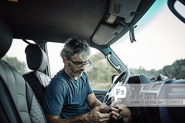 Mature man sitting sitting in his off-road vehicle checking his smartphone