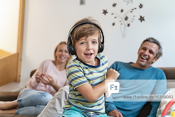 Portrait of boy listening to music with headphones on couch at home with parents in background