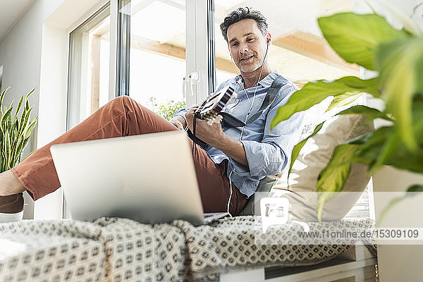 Mature man practising on the guitar  using laptop and earphones