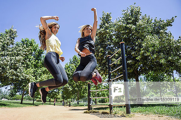 Athletic woman and her daughter jumping together in a park