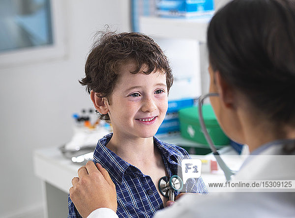Female doctor examiming a boy in a clinic