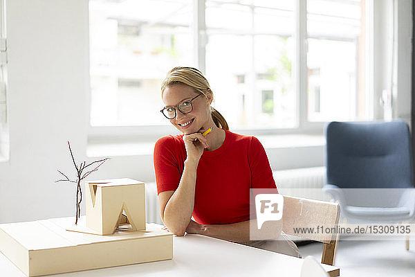 Junge Frau im Büro mit Architekturmodell auf dem Schreibtisch