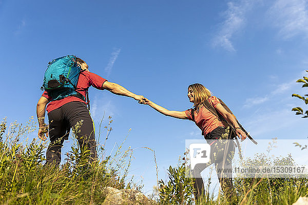 Young couple hiking in mountain meadow
