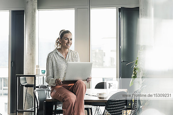 Smiling businesswoman sitting on table in office with laptop