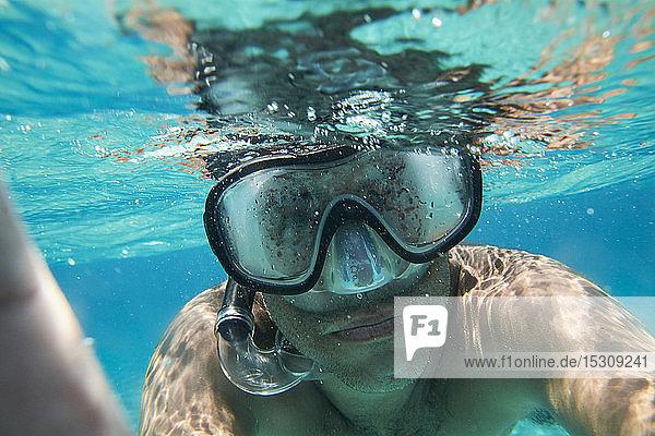 Porträt eines Mannes mit Taucherbrille und Schnorchel beim Selbstversuch unter Wasser