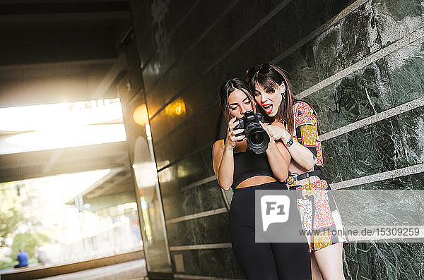 Two young woman checking photos on a camera