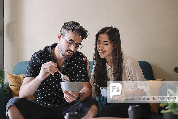Junges Paar sitzt auf einer Couch in einem Café und frühstückt
