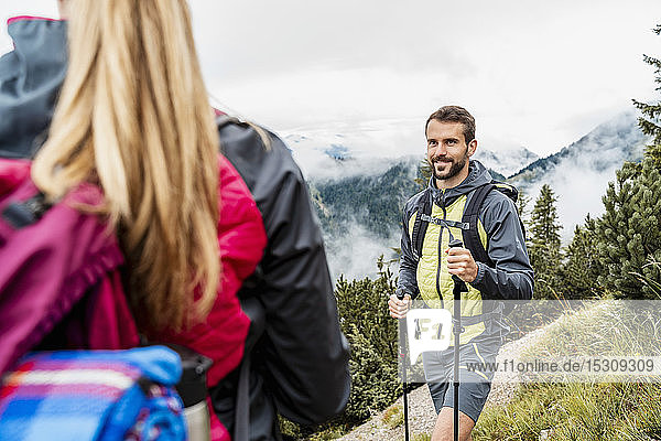 Smiling young couple on a hiking trip in the mountains  Herzogstand  Bavaria  Germany